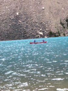 2 people paddling a canoe on a lake